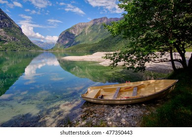 Small rowing boat moored at the shore of lake Bondhusvatnet, where the mountain sides are running all the way in to the calm waters