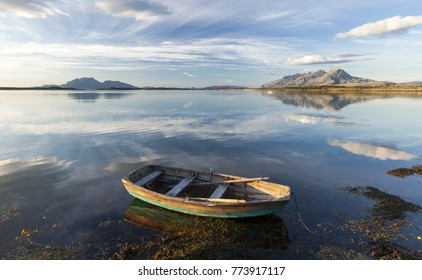 Small rowing boat. Mountains on horizon reflecting on water surface. Photographed in Helgeland, Norway.