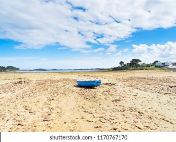 A small rowing boat sits beached on the rocky bottom of Kermengi harbour at low tide.