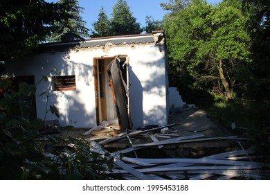 A small ruined house among greenery with a garden due to vandals and riots