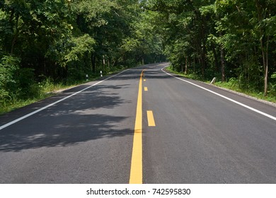 the small rural asphalted curve or bend road in Thailand.  Road in forest.