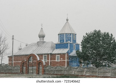 Small rural orthodox church is in a snowy weather