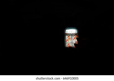 A small rural window with simple rural curtains through which light falls amidst the complete darkness of the room. Simple rural style, retro, vintage.