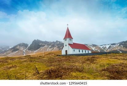 Small Rural Wooden Church in Iceland with Mountains in the background on a cloudy day