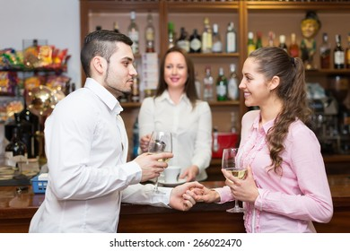 Small russian bar with female barista and two clients at counter