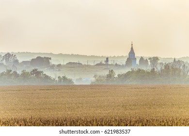 Small Russian village with a Church in the foggy horizon. Rural landscape.