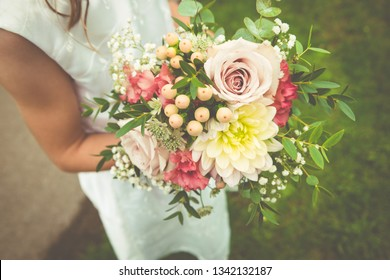 Small rustic seasonal September hand-tied wedding bouquet held by girl bridesmaid: pastel pink roses, dahlia, gypsophilia, astrantia, berries, foliage