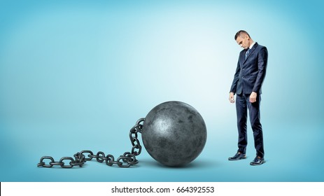 A small sad businessman looking down to a giant iron ball and chain on blue background. Job restrictions. Business bounds. Credit burden.