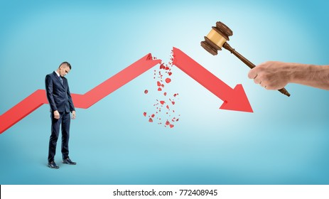 A small sad businessman stands near a red statistic arrow broken by a giant hand holding a judge gavel. Business failure. Corporate law. Cost of legal action.