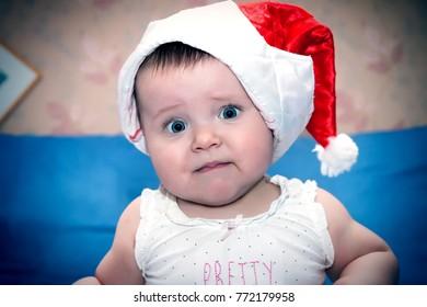 A small sad girl in a Santa cap