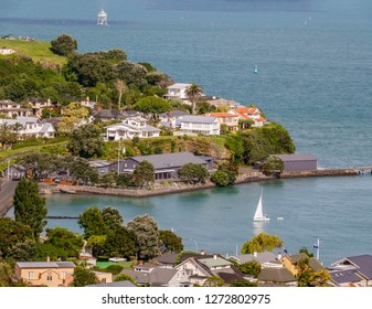 Small sailboat towing dinghy across Torpedo Bay approaches boat ramp in Devonport, a suburb of Auckland, New Zealand, on a summer day, with landmark Bean Rock Lighhouse in Mission Bay at upper left