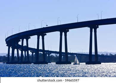Small sailboat under the San Diego - Coronado Bridge, locally referred to as the Coronado Bridge, crossing over San Diego Bay in the United States, linking San Diego, with Coronado, California.