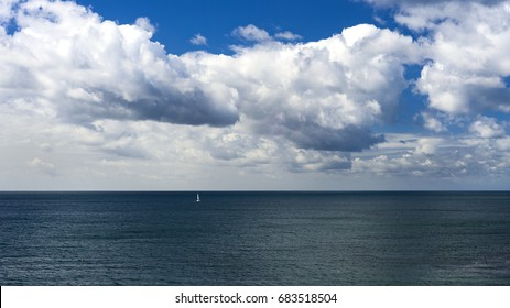 A small sailing boat made its way out towards the big blue looking rather insignificant amongst the gigantic clouds surrounding it.