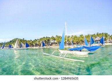 Small sailing boats for touristic excursions at sunset in Boracay island - Exclusive travel destination in Philippines - Vivid sunny filtered look