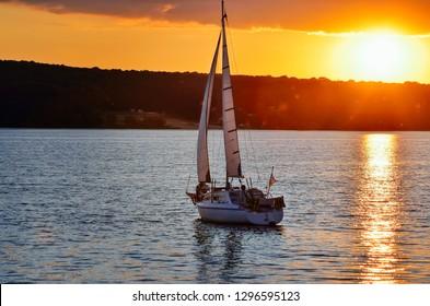 A small sailing ship sailing on a calm sea at the sunset