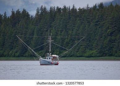 Small salmon fishing boat in a protected cove in Southeast Alaska in summer.