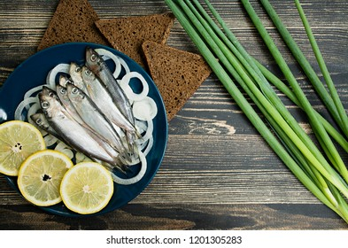 Small salted fish of Baltic herring, sprats on a wooden table. Top view.