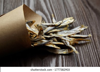 Small salted stockfish heap in paper bag on dark wooden table background. Beer snack.