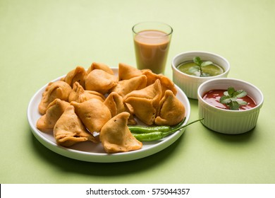 small samosa in wooden bowl with sauce and hot tea