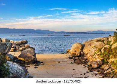 Small sand cove between granite coastal rocks in Arousa Island
