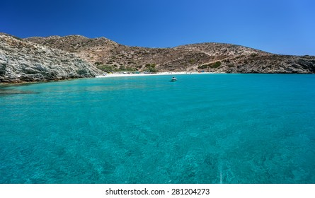Small sandy beach with transparent waters and a small anchored boat, in Donousa island, Cyclades, Greece