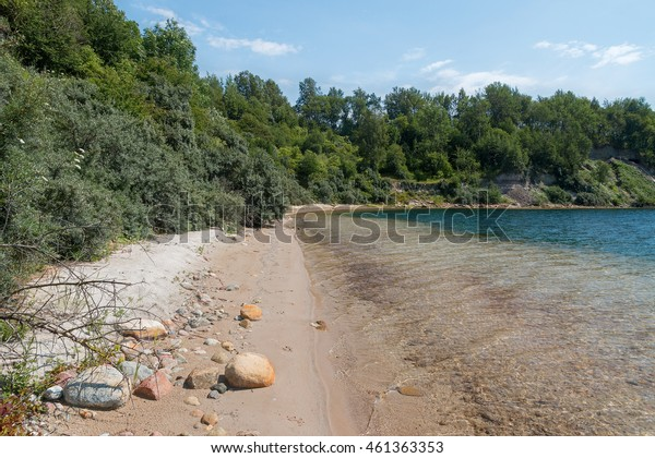 Small sandy beach at the wild shore of azure lake
