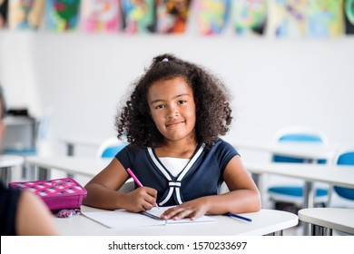 A small school girl sitting at the desk in classroom, writing.