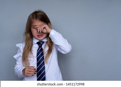 Small schoolgirl covering face, crying portrait. Preteen stressed, scared child hiding, wiping off tears. Pupil, student in school uniform. Back to school, sad, miserable young girl ready for class
