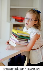 The small schoolgirl of an elementary school is tired. To the child difficultly long to be engaged. The girl has embraced a pile of textbooks and looks into the camera with tired eyes.