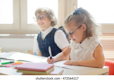 Small schoolkids in the lesson. It's elementary school students. Girl diligently writes, boy idles. On a school desk there are textbooks and school accessorie.