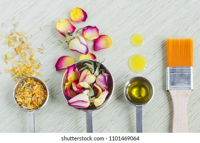 Small scoops with dry rose buds, marigold flowers, essential rose oil or olive oil and cosmetic brush. Ingredients of diy masks for natural skin and hair care. Homemade cosmetics concept. Copy space.