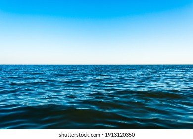 Small sea waves against the blue sky and white horizon - Shutterstock ID 1913120350