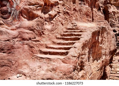 A small series of stone steps, as an old stairway, leads up the side of a cliff to the Urn Tomb on the edige of the ancient city of Petra in Southern Jordan.