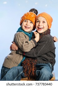 Small Series of two Bothers with orange hats in Winter Snow Background: Hapiness over the cold season