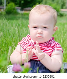 Small serious baby girl sitting on the grass in a field in a striped dress