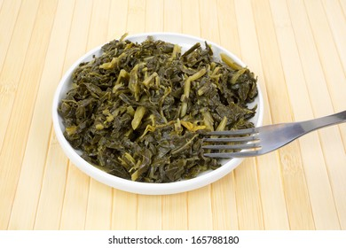 A small serving of collard greens in a dish with a fork.