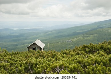 Small shed/house with view of Carpathian mountains during summer day.