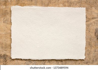 small sheet of blank white Khadi rag paper from South India against brown amate bark paper