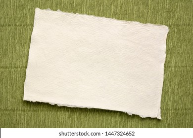 small sheet of blank white Khadi rag paper from South India against green Italian crepe paper