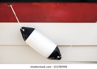 Small ship bump element hanging above white and red yacht hull