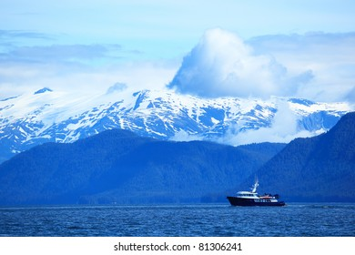 The small ship floats on snow mountains of Alaska  background