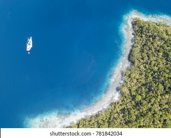 A small ship rests at anchor near a beautiful tropical island in Raja Ampat, Indonesia. This region is known as the heart of the Coral Triangle due to its high marine biodiversity.