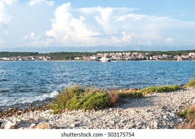 A small ship sailing along Zadar town in a deep blue sea water. Sunny summer day, fluffy clouds in the sky