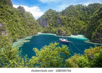 A small ship is tied to limestone islands in a gorgeous lagoon near Misool, Raja Ampat, Indonesia. This tropical region is known as the heart of the Coral Triangle due to its marine biodiversity.