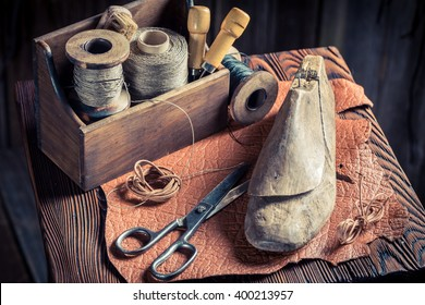 Small shoemaker workplace with tools, leather and shoes