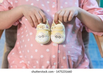 Small shoes for the unborn baby in the belly of pregnant woman. Pregnant woman holding small baby shoes relaxing at home in bedroom. Small shoes for the unborn baby in the belly of pregnant woman