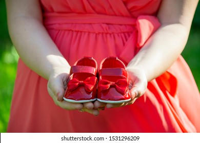 Small shoes for the unborn baby in the belly of pregnant woman. Pregnant woman holding small baby shoes relaxing and wearing pink dres Small shoes for the unborn baby in the belly of pregnant woman