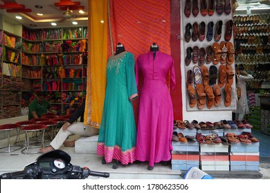 Small shop owner indian man selling shawls, clothing and souvenirs at his store. Colorful traditional Indian costume/outfit for women on mannequins. : Udaipur India - June 2020