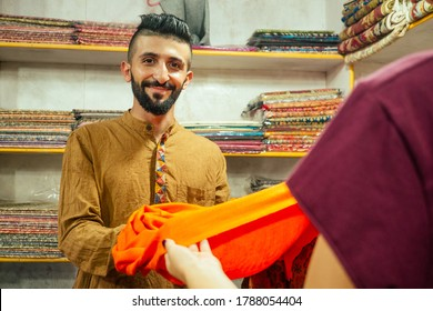 small shop owner indian man selling shawls at his store in arambol goa