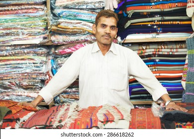 small shop owner indian man selling shawls, clothing and souvenirs at his store